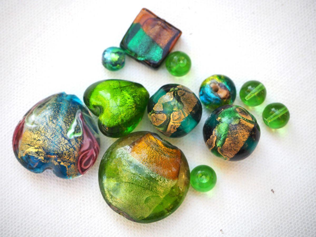 Lot de 12 perles en verre différentes, tons vert foncé avec reflets or