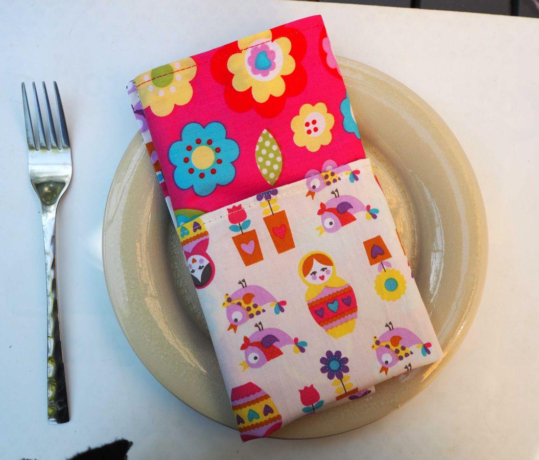 28- Serviette de table 33x33cm, fond rose avec motifs fleurs vintage et fond rose pâle poupées russes
